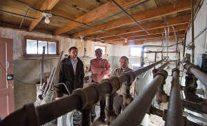 (left to right) NREL's Jesse Dean, Wally Piccone from the City of Lakewood, and NREL's Frank Rukavina assess the utility room at the City of Lakewood's Graham House. NREL is coordinating a joint effort with the City of Lakewood and Red Rocks Community College to audit the Graham House and make suggestions for sustainable and energy-efficient modifications. The property was donated to the City and is used for public meetings and events. Credit: Dennis Schroeder Courtesy of NREL