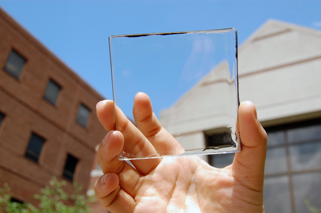 Solar power with a view: MSU doctoral student Yimu Zhao holds up a transparent luminescent solar concentrator module. Photo by Yimu Zhao.  Courtesy of MSU